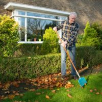 oudere man harkt de tuin