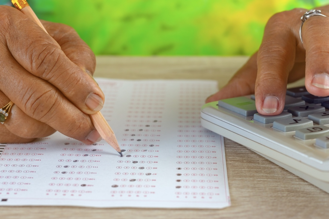 handen van vrouw die een test doet op vragenlijst en computer